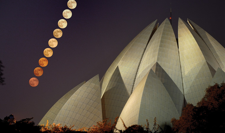 full moon rising over lotus temple penumbral eclipse